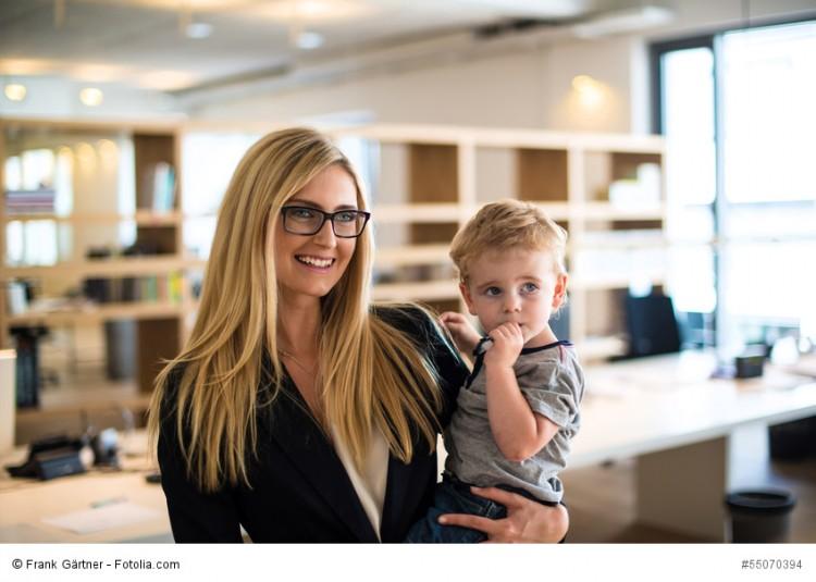 Blonde Frau im Büro mit kleinem Kind auf dem Arm