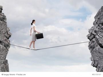 Geschäftsfrau geht auf einem Seil über einen Abgrund