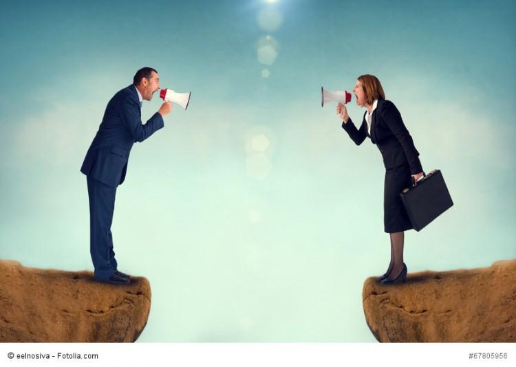 Mann und Frau schreien sich mit Megafon über eine Klippe hinweg an