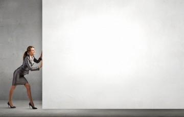 Businessfrau schiebt eine Wand weg - langer Weg zur Gleichstellung