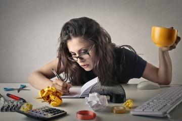Frau mit gelber Tasse an chaotischem Schreibtisch