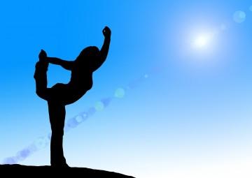 Frauen macht Yoga vor blauem Himmel
