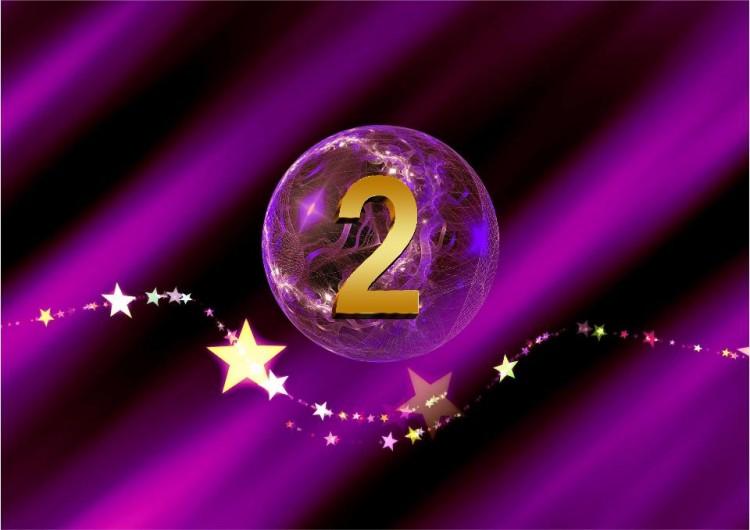 Lila Kugel mit goldener 2 und goldenem Sternenband für den SHEworks Adventskalender
