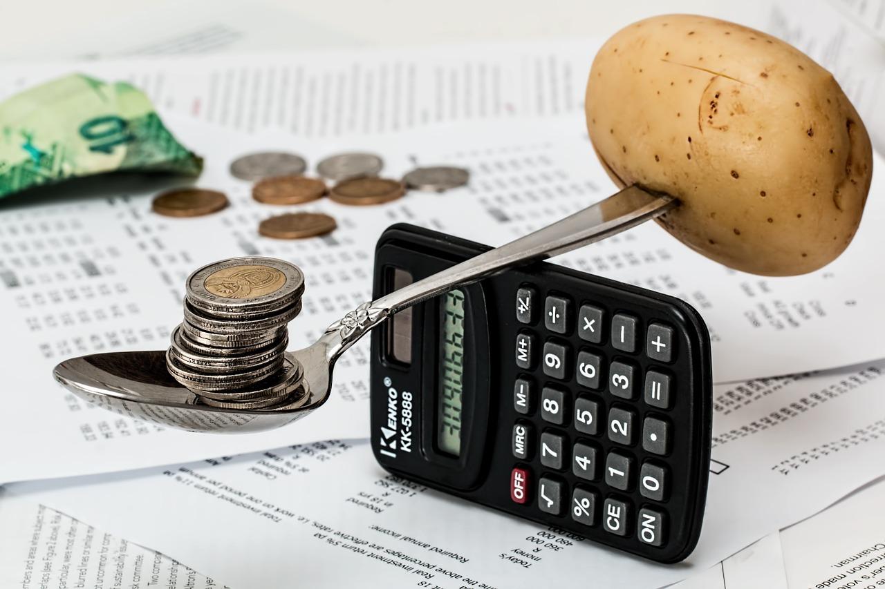 soziale Absicherung für Solopreneure - Löffel als Waage mit Geld und Kartoffel balanciert auf einem Taschenrechner