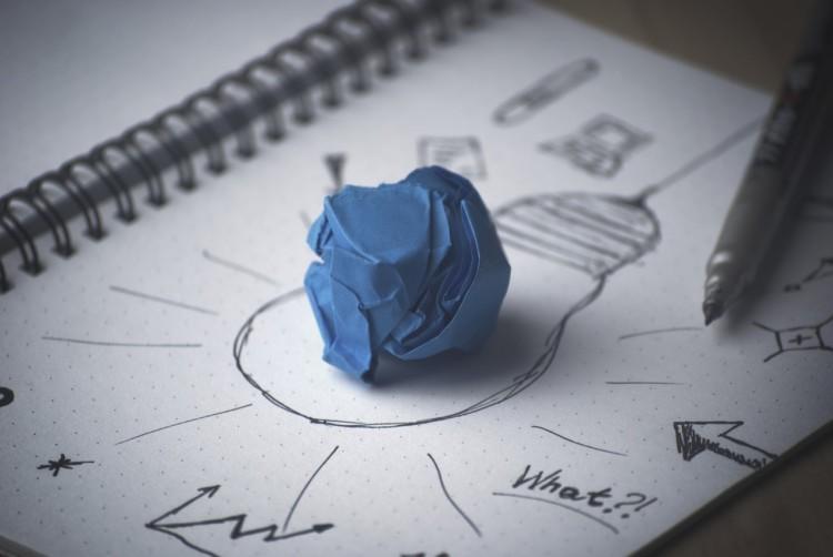Notizbuch mit Papierknäuel auf einer gemalten Glühbirne - Kreativität
