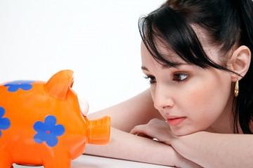 Frau schut Sparschwein an - Equal Pay Day will Lohnlücke bekämpfen