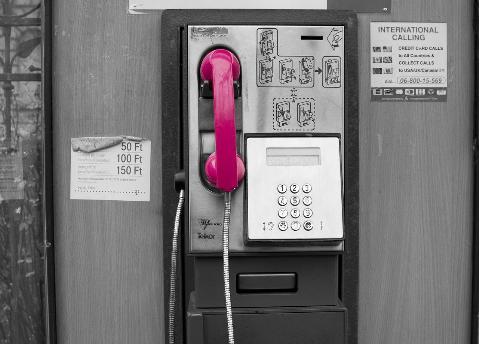 Pinker Telefonhörer an Münzfernsprecher - Online-Frauenbranchenbuch