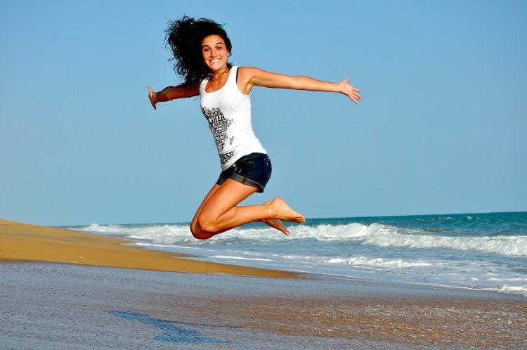 Frau springt am Strand in die Luft - Frauen in der Gesundheitsbranche