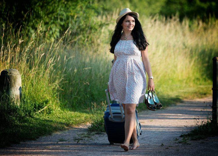 Frauen in der Reisebranche - Frau mit Koffer und Schuhen in der Hand auf einem Waldweg