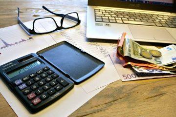 Forderungsmanagement wenn der Kunde nicht zahlt Arbeitsplatz mit Brille, Laptop, Taschenrechner, Rechnung, Geld
