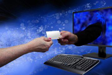 Frauenhand reicht Visitenfarte zu Männerhand, die aus dem Bildschirm kommt - netzwerken im digitalen Zeitalter