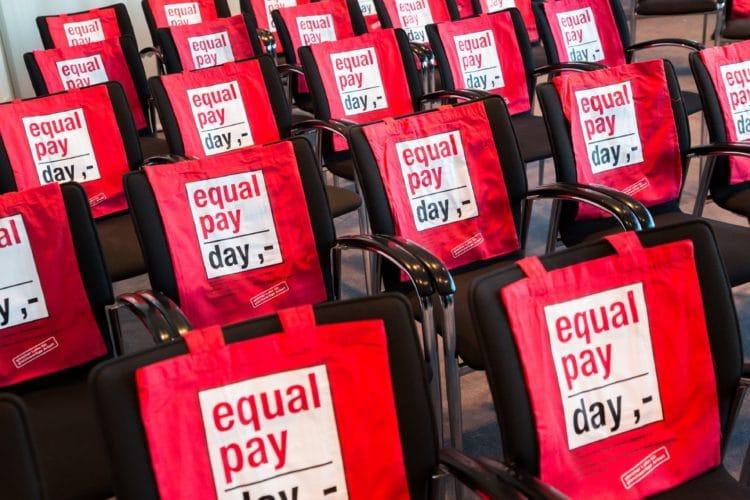Stühle mit roten Equal Pay Day Taschen über der Rückenlehne