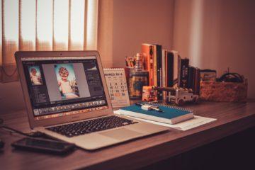 Laptop mit Kinderfotos im Homeoffice, nebenberuflich selbststaendig