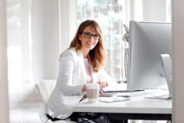 Portrait of attractive businesswoman sitting at her desk looking happy while working at office in front of computer.