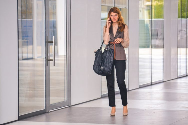 Frau mit großer Tasche und legerer Businesskleidung