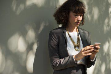 Frau mit Handy trägt einen Anzug, weiße Bluse und auffällige Kette